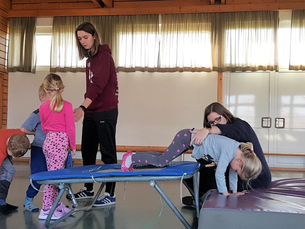 Kinderturnen - Hilfestellung beim Rolle machen